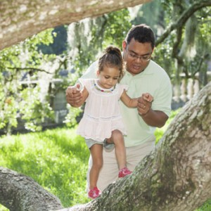 Photo of dad with daughter climbing tree