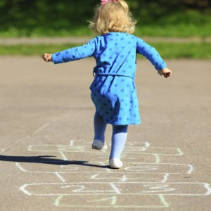 Photo of toddler playing hopscotch